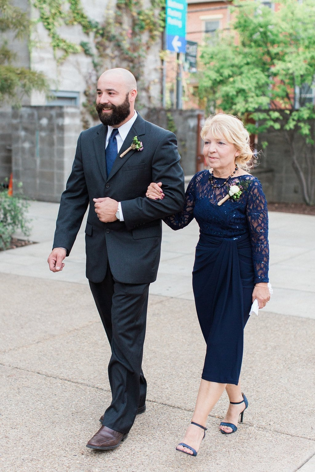 Groomsman walking mother of the bride wearing a blue dress down the aisle
