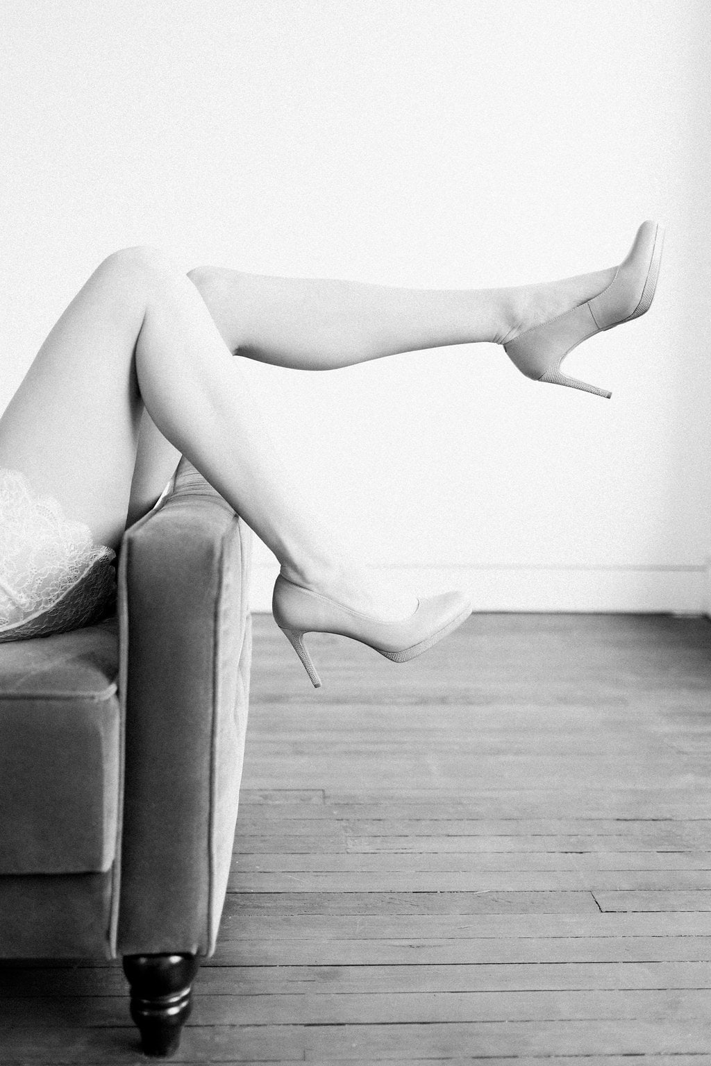 Black and white photo of brides legs with heels on