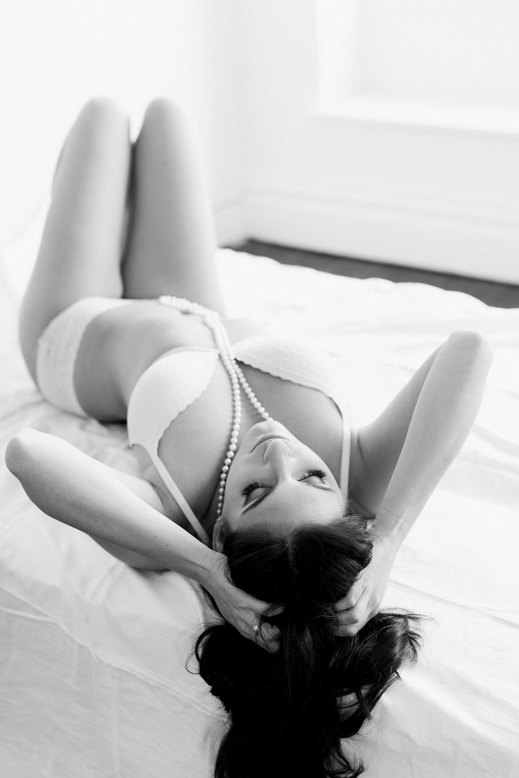 Black and white image of bride laying on her back in lingerie