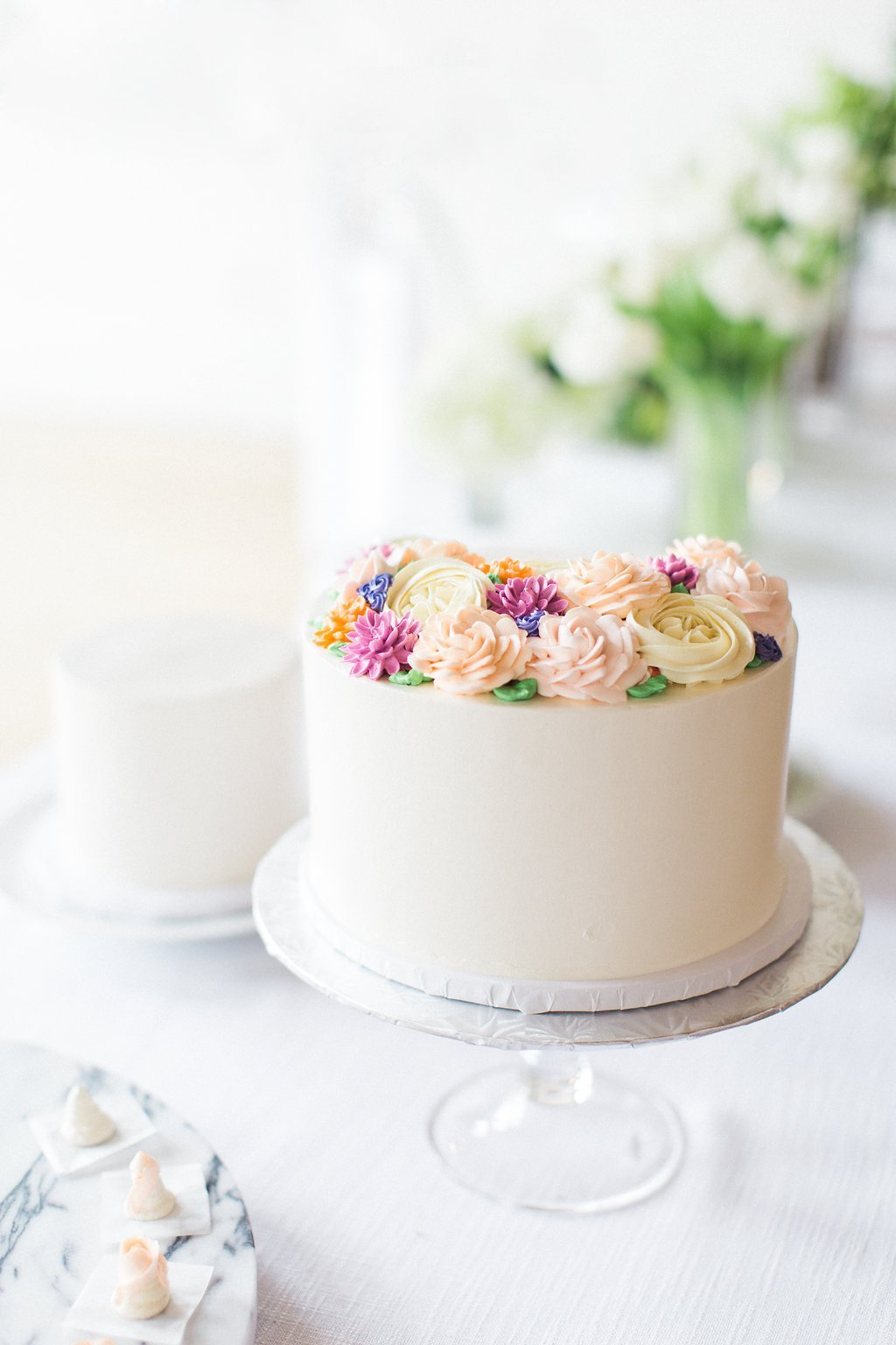 white one tiered cake with butter cream frosting flowers