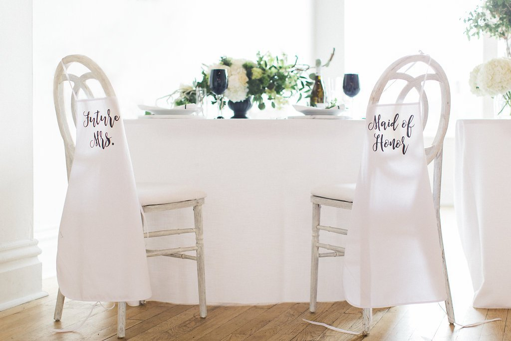 table set up with white cane back chairs and aprons with calligraphy