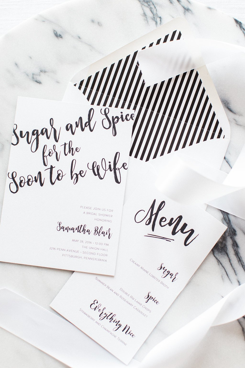 black and white invitation styled on marble board
