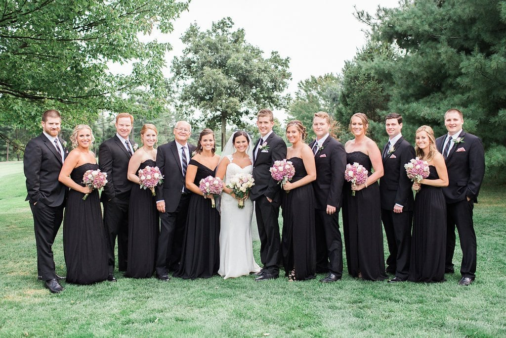 Bridal party on golf course bridesmaids wearing black with pink bouquets