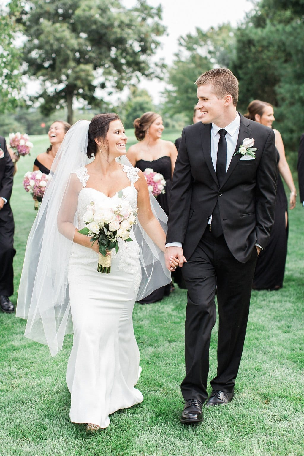 Bride and groom walking and holding hands looking at each other with bridal party