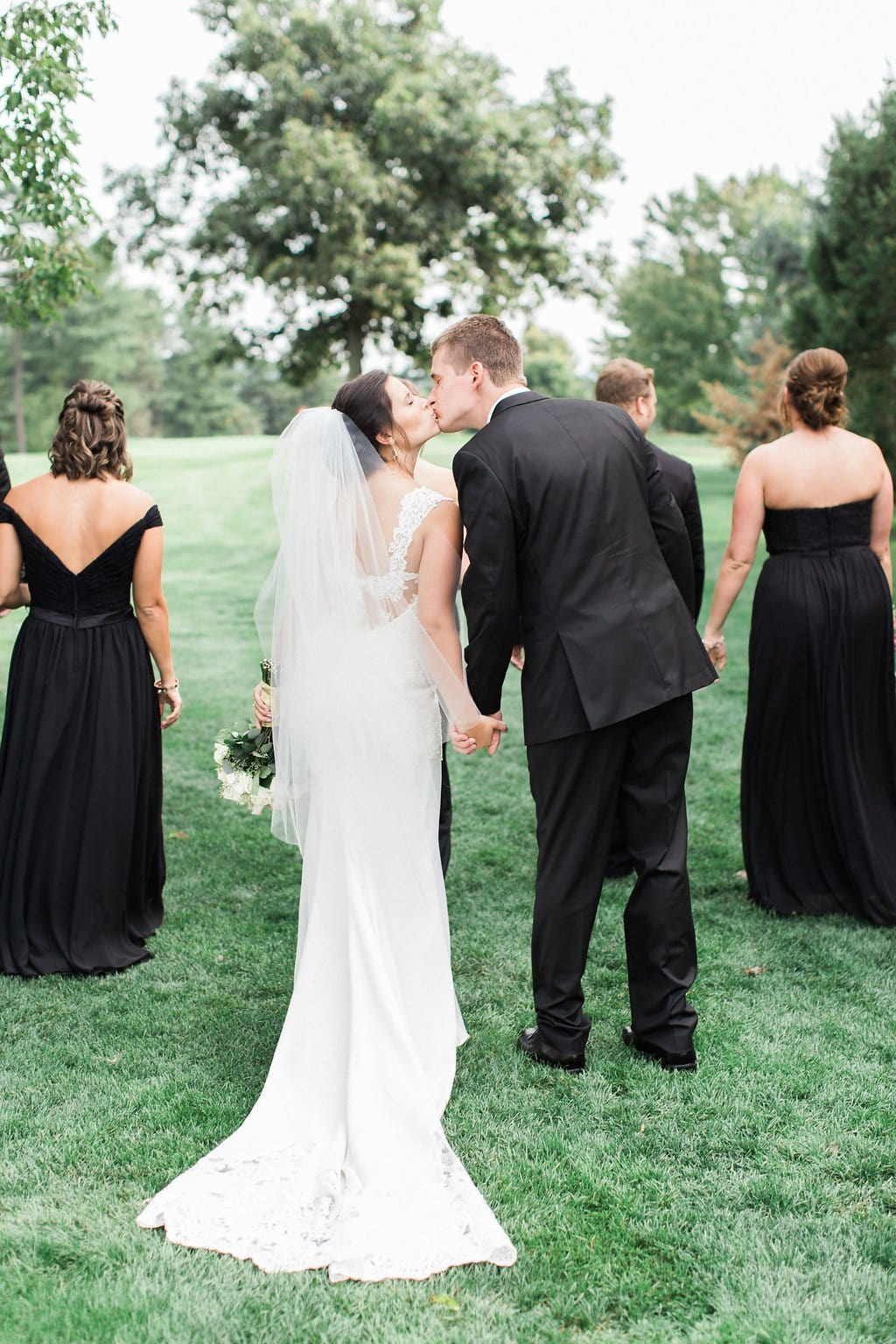 Bride and groom kissing while holding hands and walking with bridal party on golf course