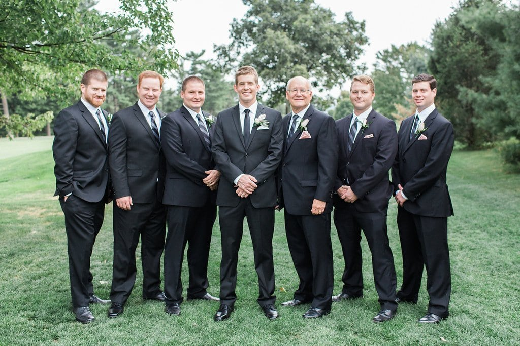 Groomsman standing for formal photo wearing black tuxes