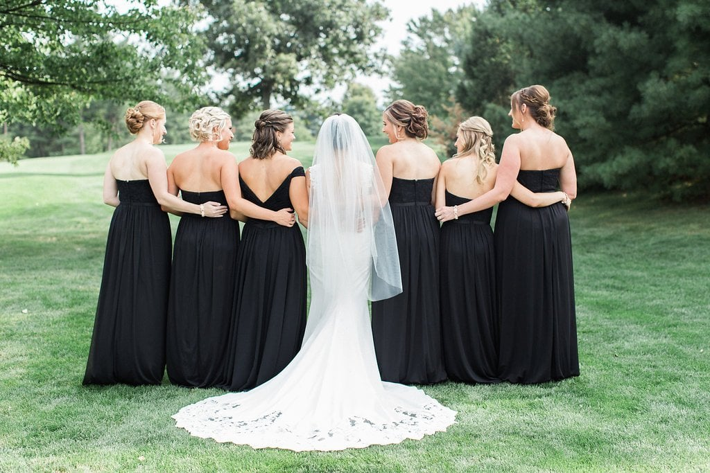 Bridesmaids standing together for formal photo in black dresses while looking at the bride
