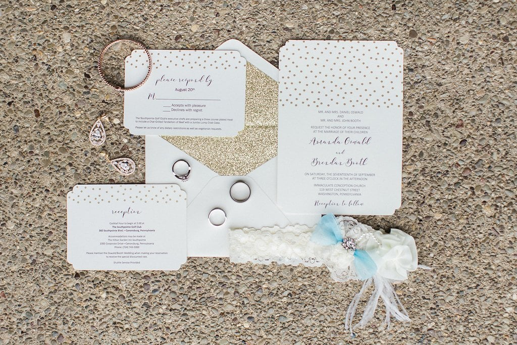 Invitations, rings, jewelry, and garter in a lay flat