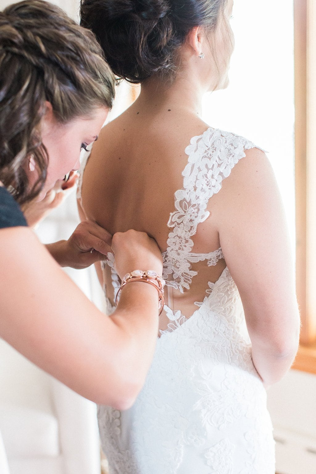 Bride's sister helping her into her wedding dress