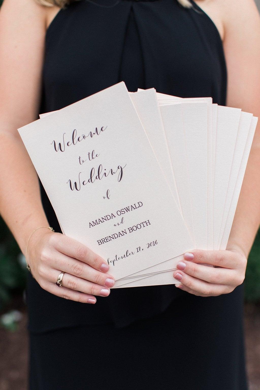 Bridesmaid holding wedding programs