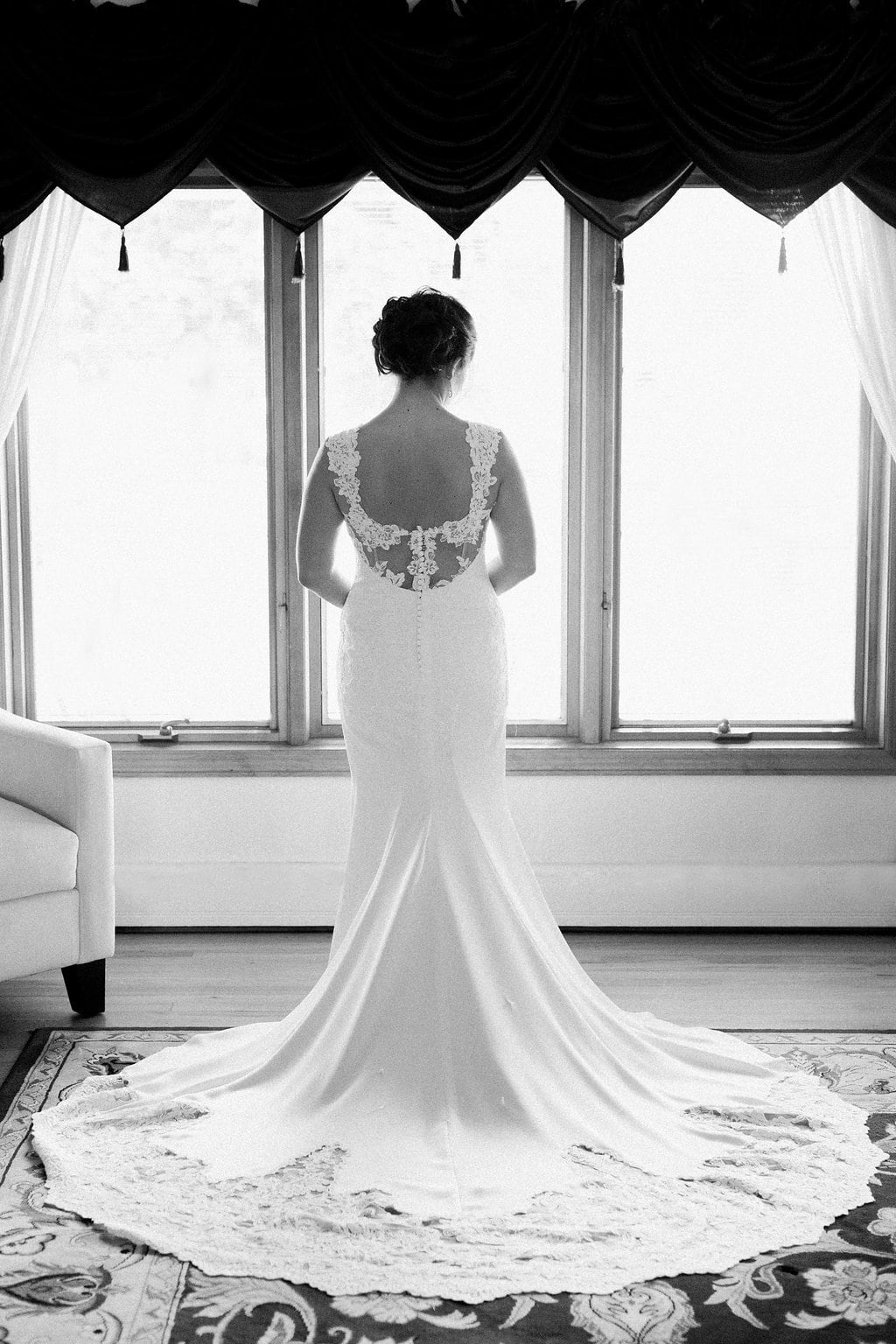 black and white photo of the bride standing in her wedding dress in her childhood home
