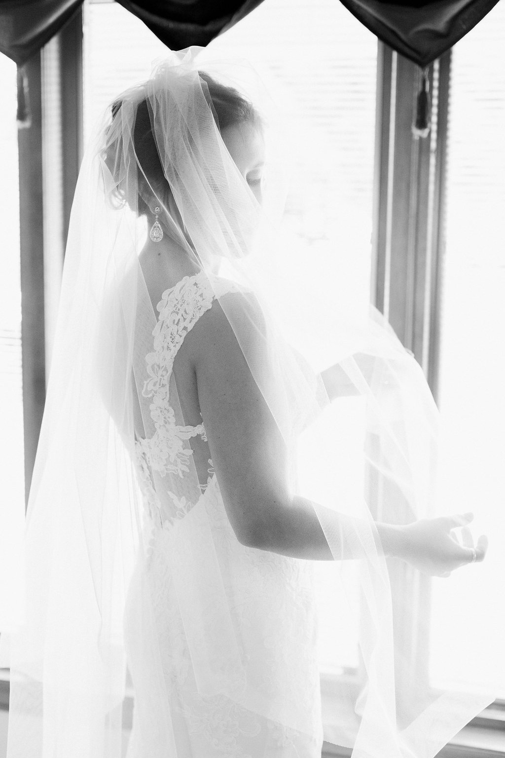 Black and white photo of bride wearing her veil