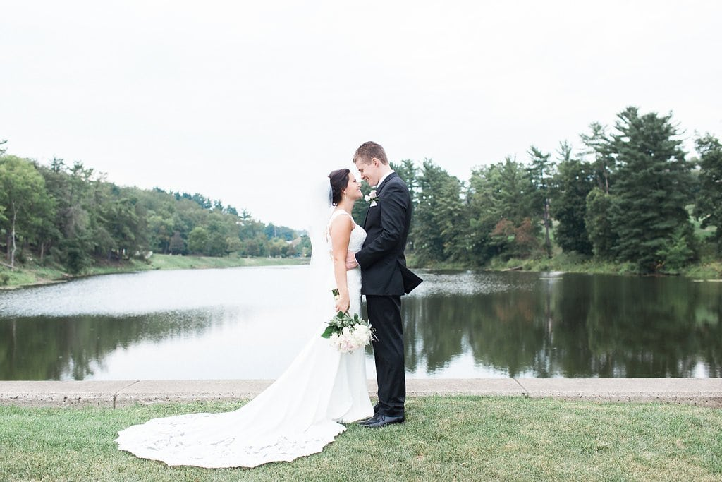 Bride and groom standing next to lake on golf course