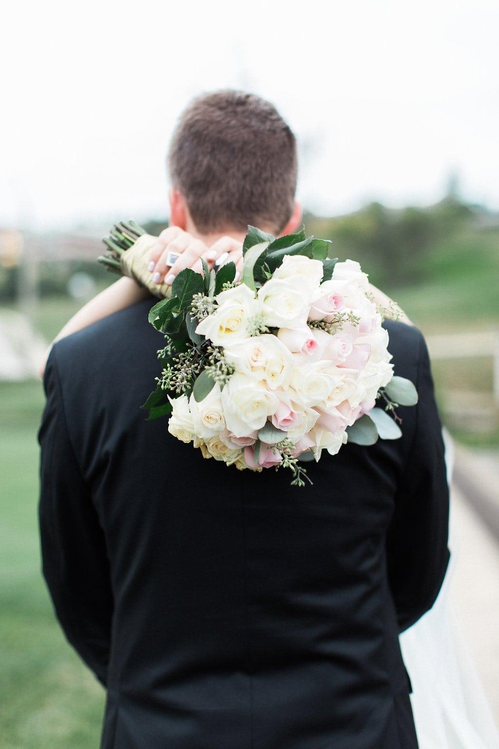 Bride putting her hands over the groom's shoulders with her bouquet