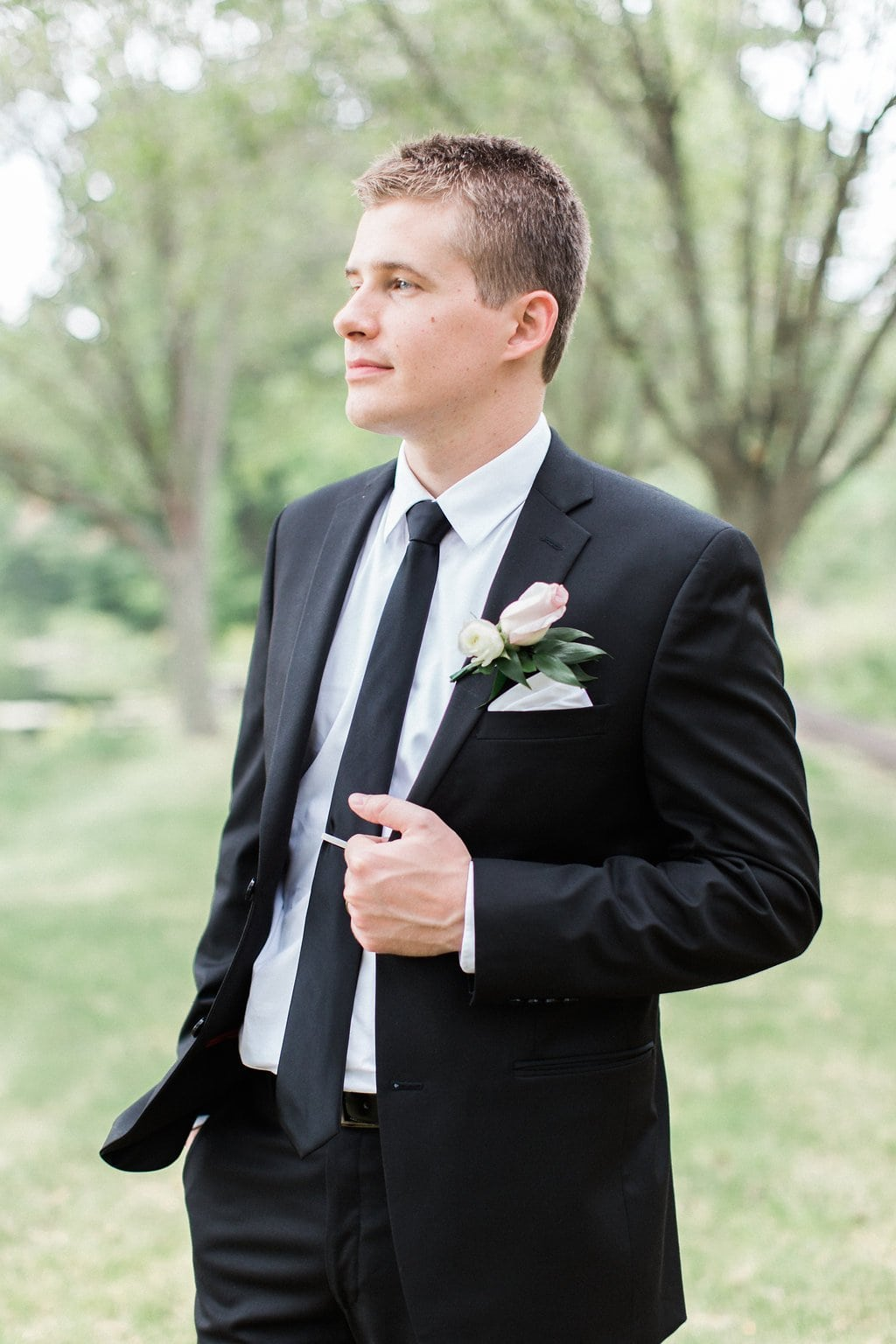 Groom posing in his black tux while holding his lapel