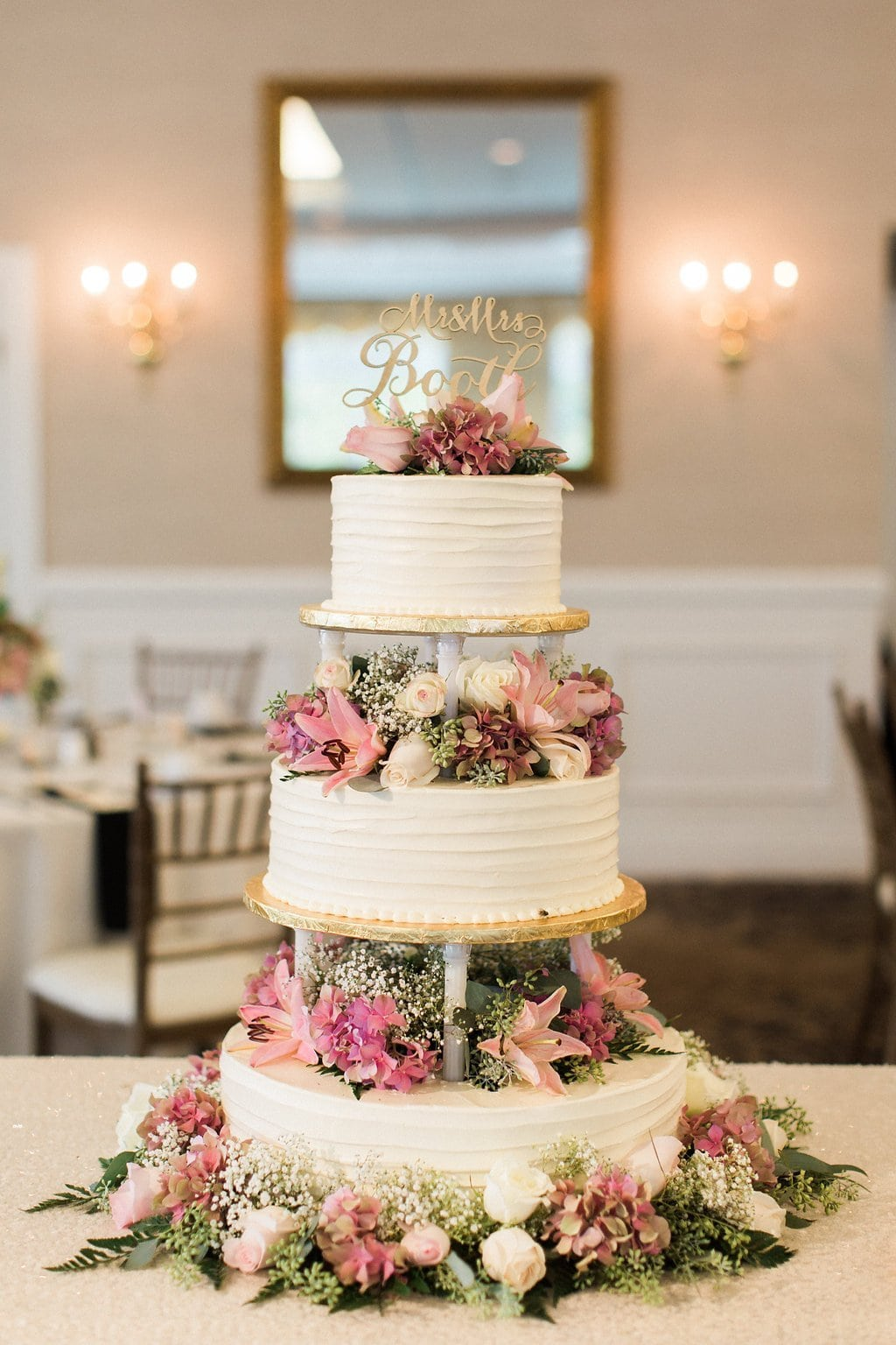 Three tied wedding cake with pink flowers and laser cutout topper