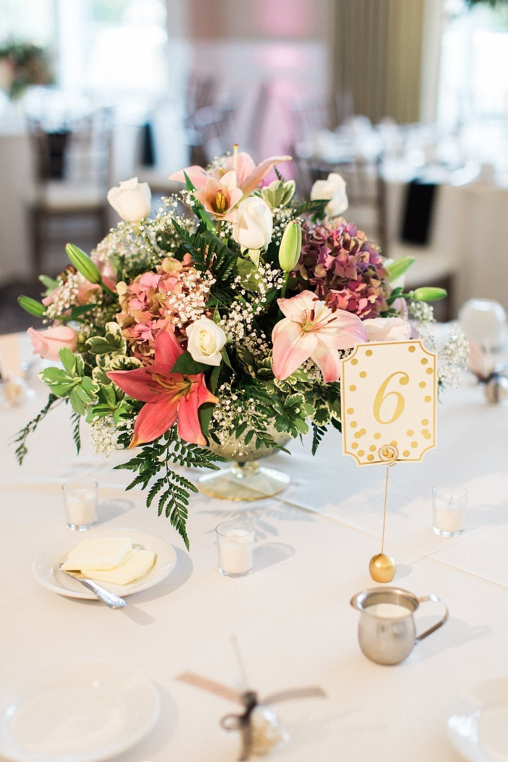 Gold dots on table numbers with pink flowers for centerpieces