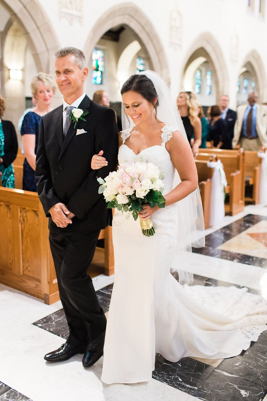 Bride smiling as she is walked down the aisle by her father
