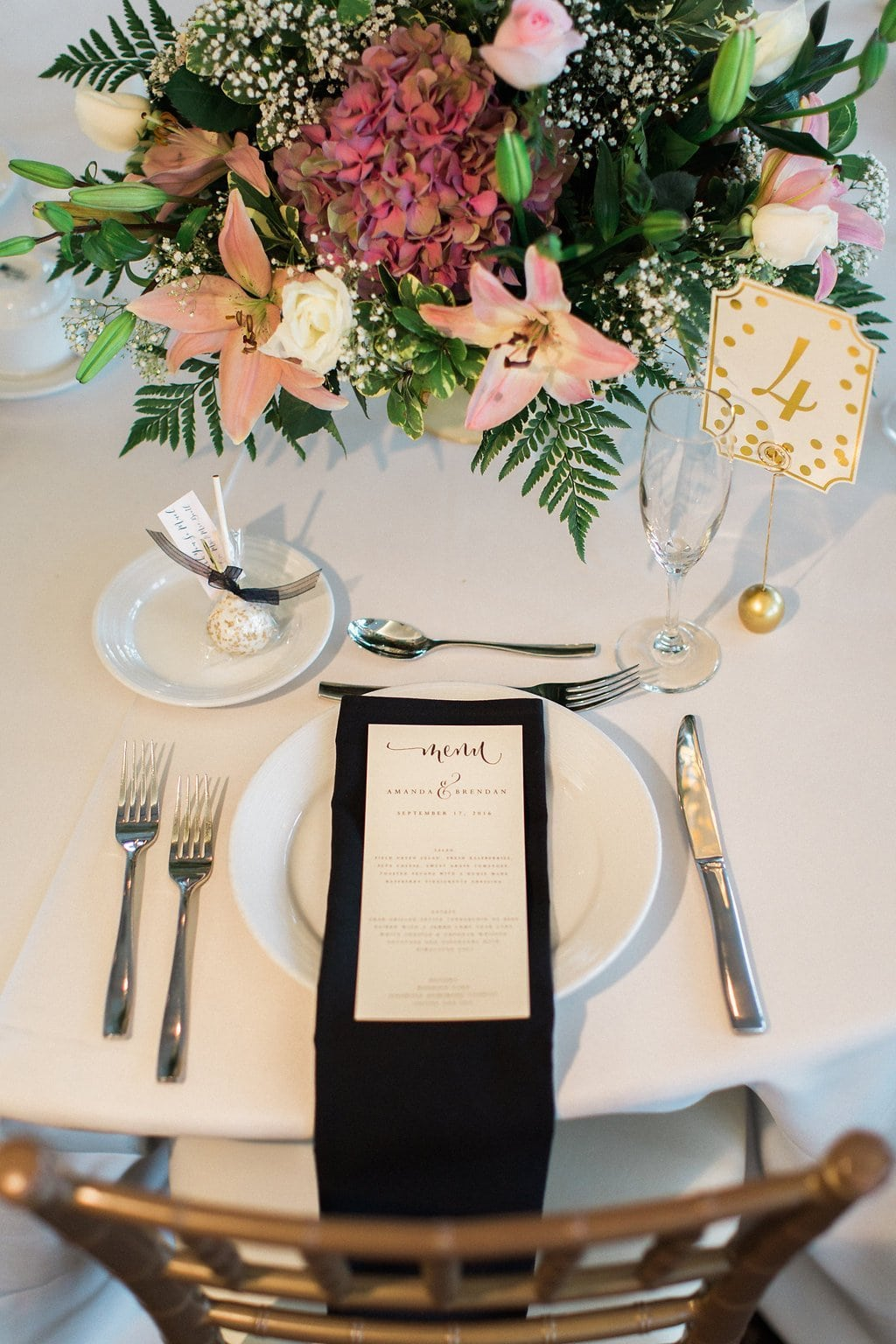 Pink flowers and black napkin accents and gold lettered table numbers for center pieces at reception