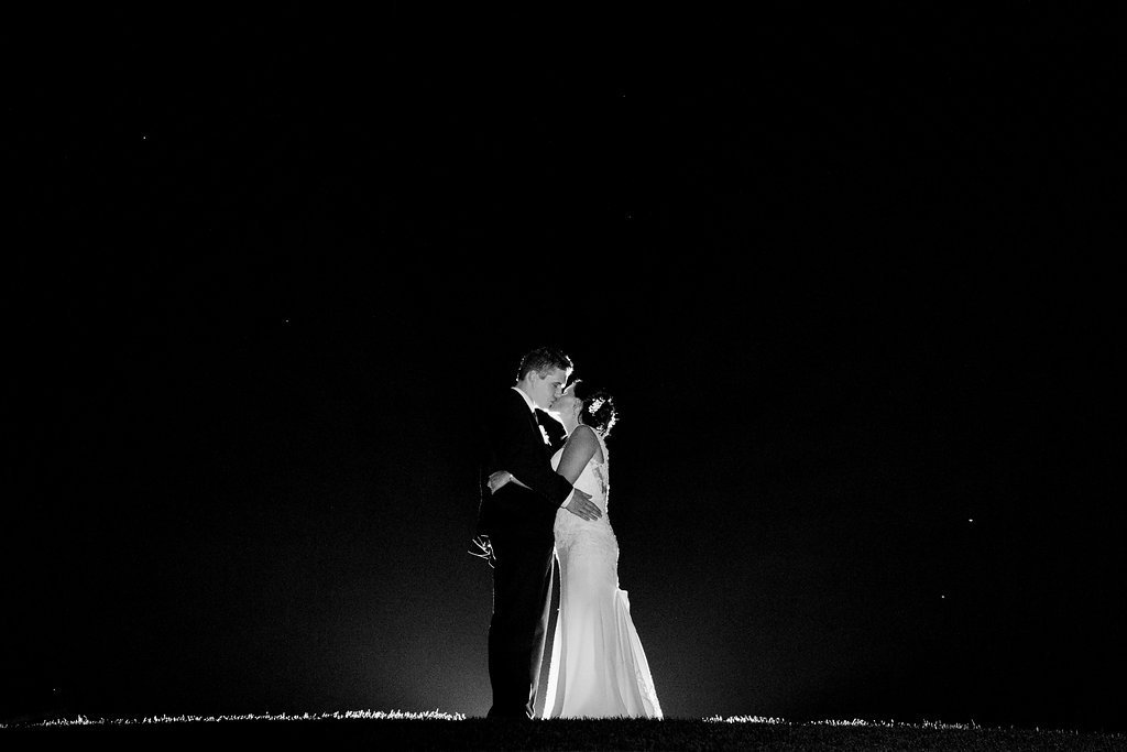 Black and white outside night photo with backlighting using flash of bride and groom kissing