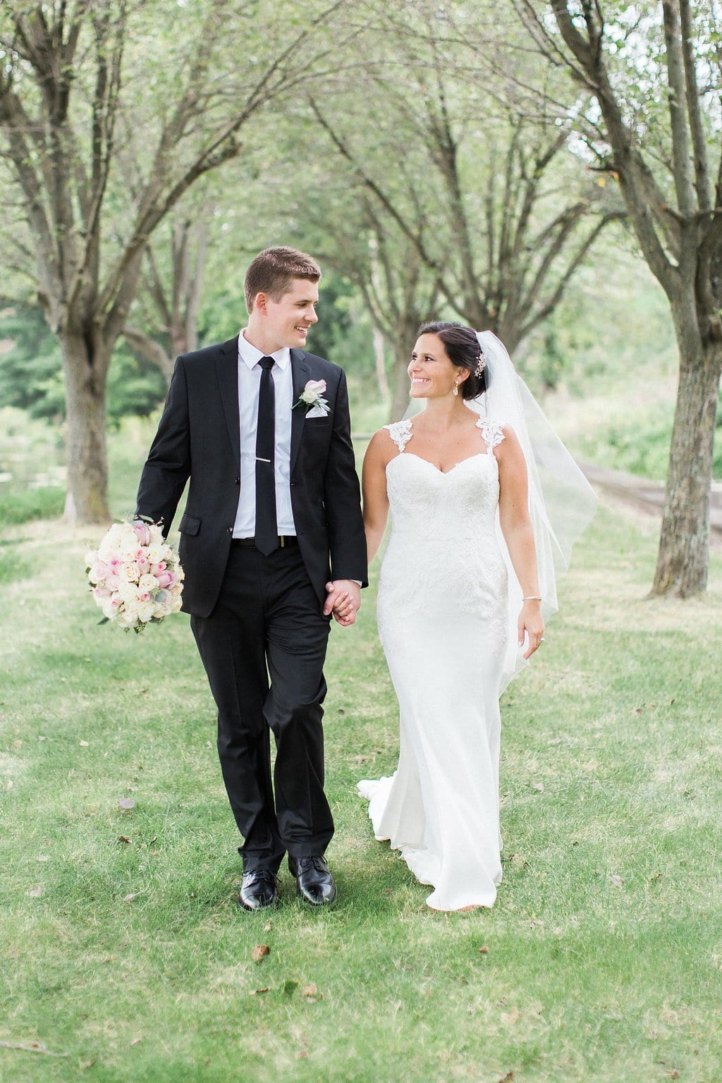 Groom holding bride's bouquet as they walk together holding hands and looking at each other