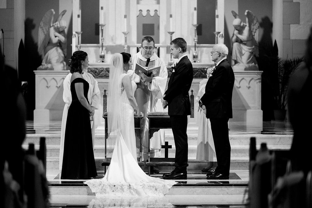 Black and white photo of the bride and groom saying their vows in church