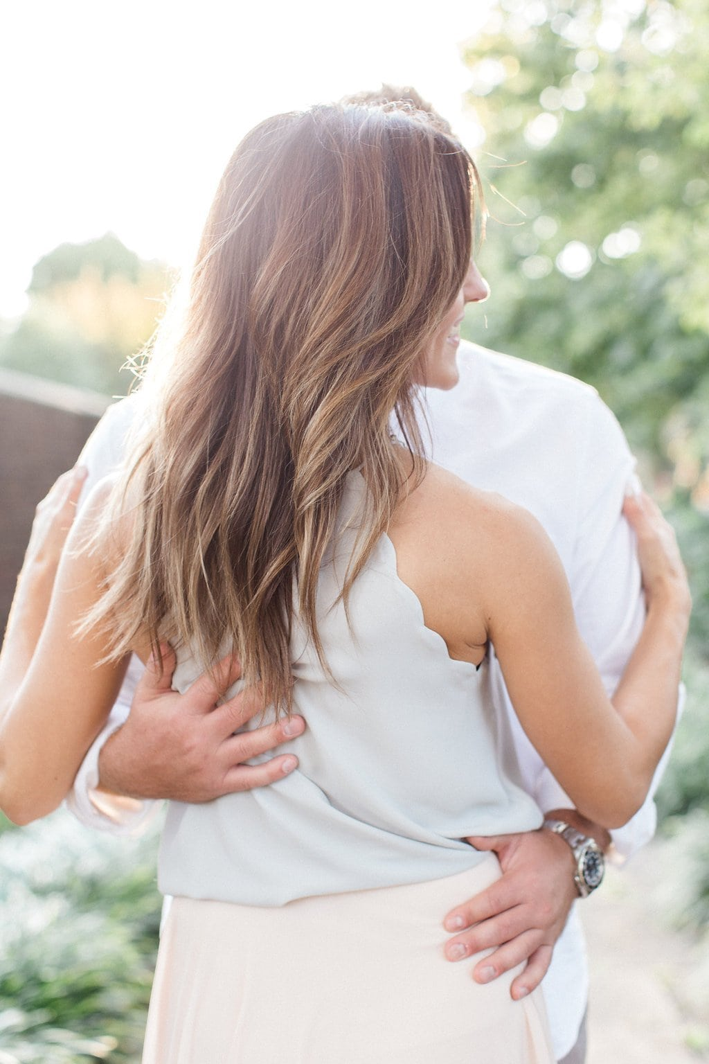 Side view of woman's hair cascading down her back while man embraces her