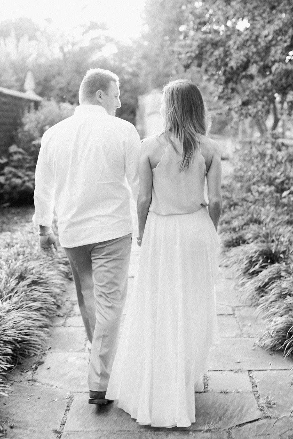 Black and white photo of couple walking away looking at each other
