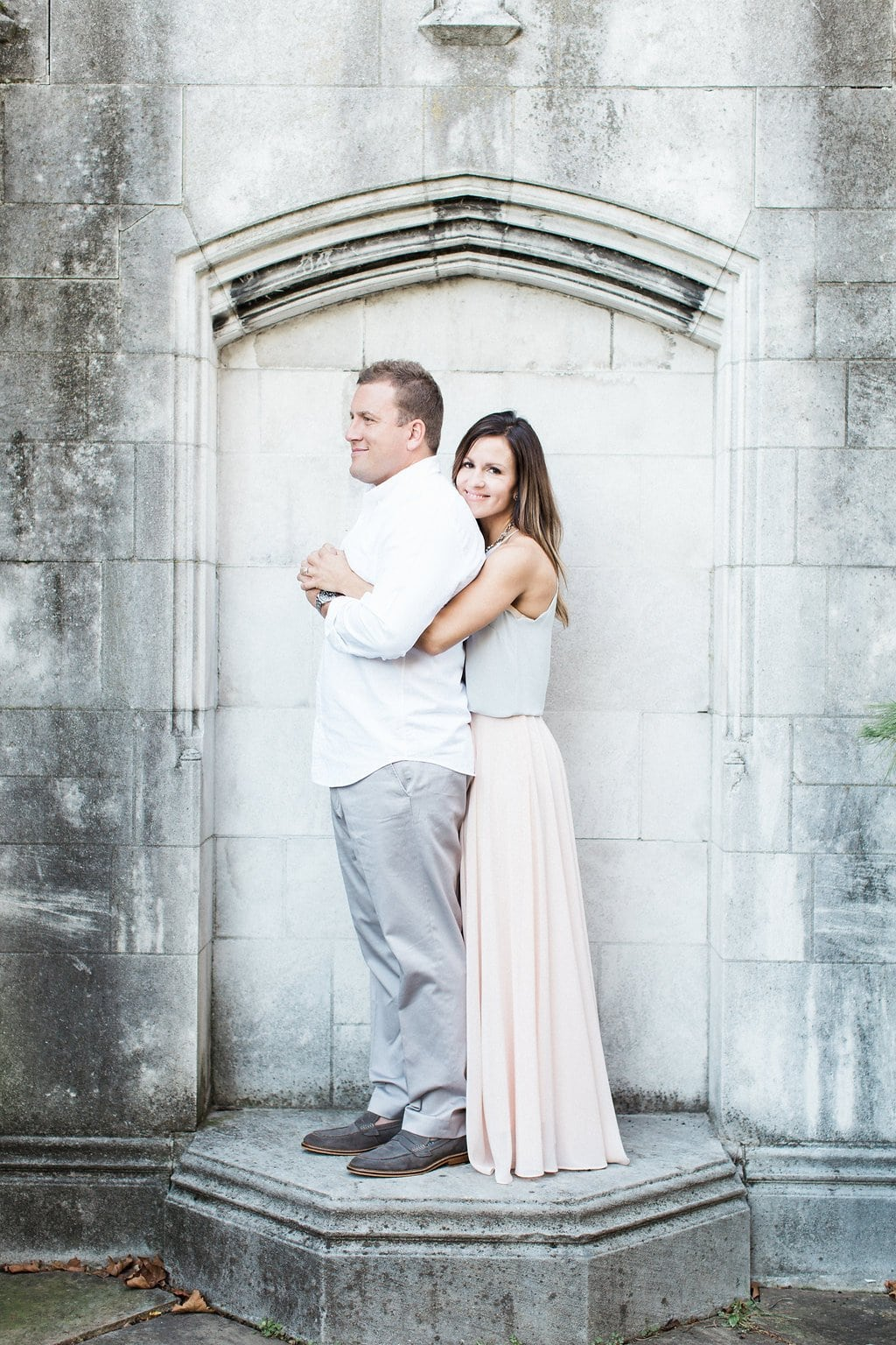 Bride cuddling up to her groom wrapping her arms around him while standing next to stone wall