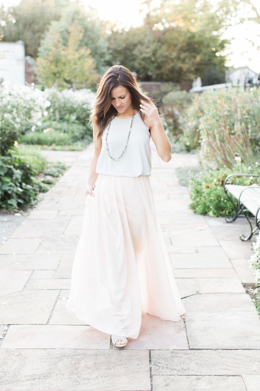Bride walking wearing a light grey sleeveless top and flowing light pink skirt