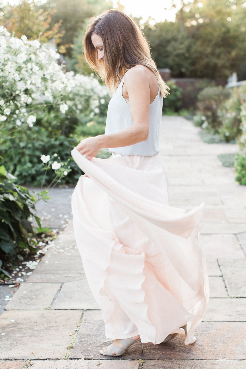 Bride dancing in the park wearing a light pink flowy skirt and grey sleeveless top