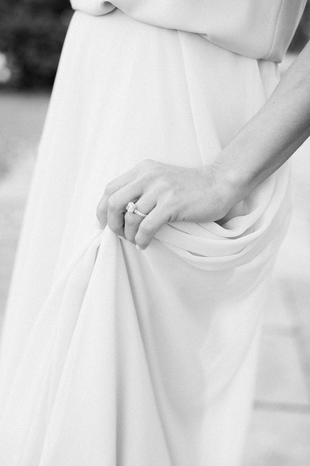 Close up of woman's engagement ring as she lightly grabs her skirt