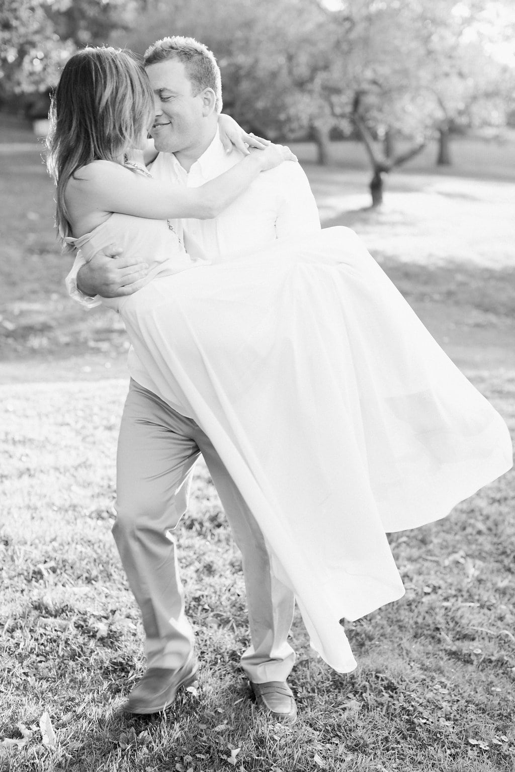 Black and white photo of groom carrying his bride across a field
