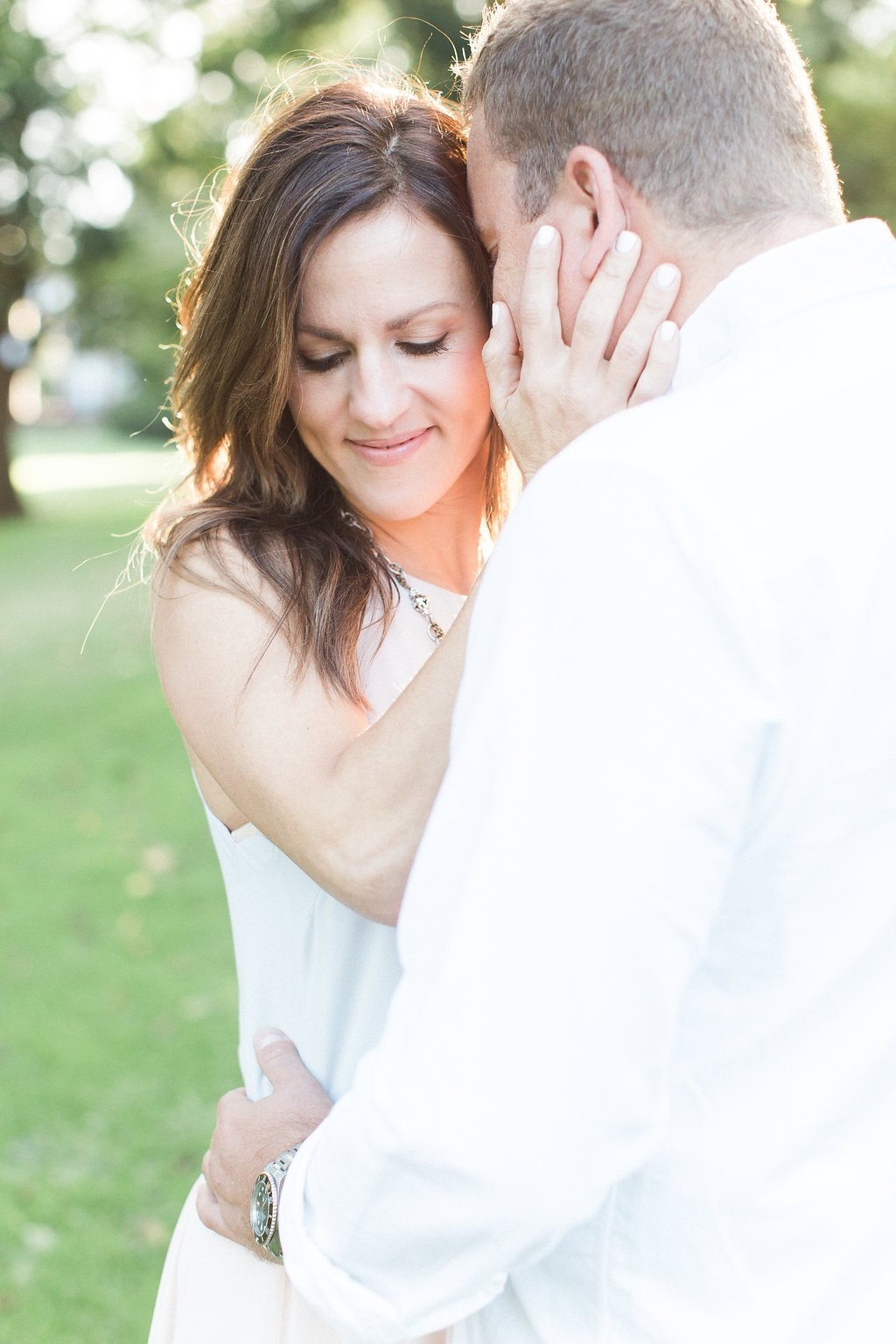 Couple cuddling during their sun kissed engagement session