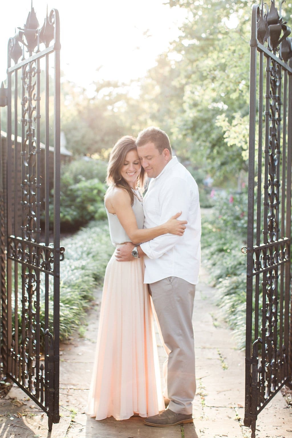 Bride and groom standing together embracing in between wrought iron gates