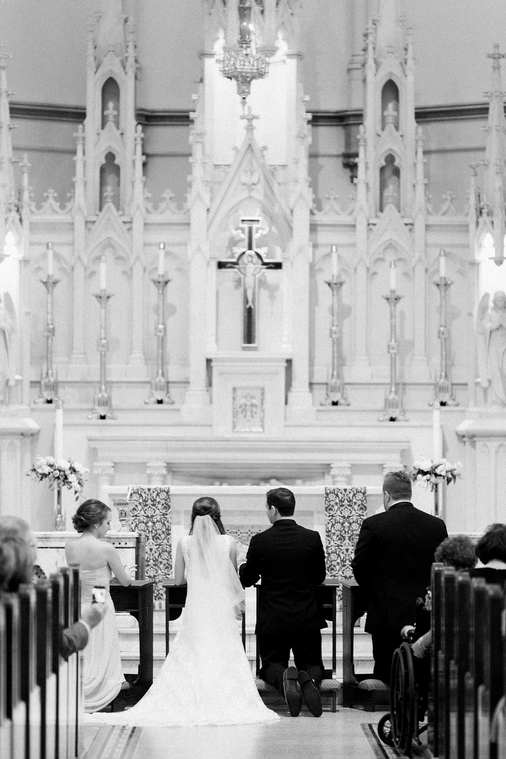 Bride and groom kneeling at church altar during wedding ceremony