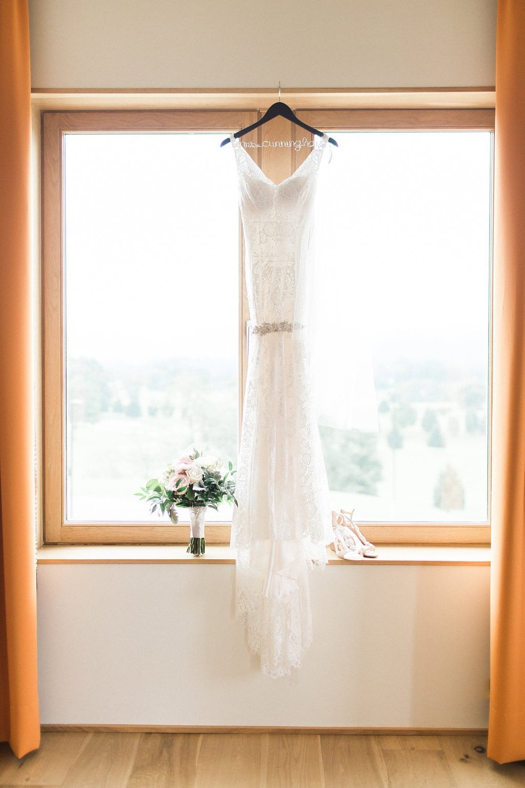 Wedding dress hanging in window with shoes and bouquet