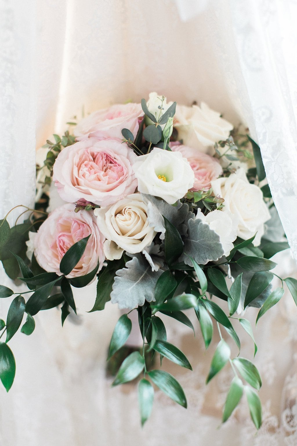 Close up of bride's light pink and white bouquet with veil