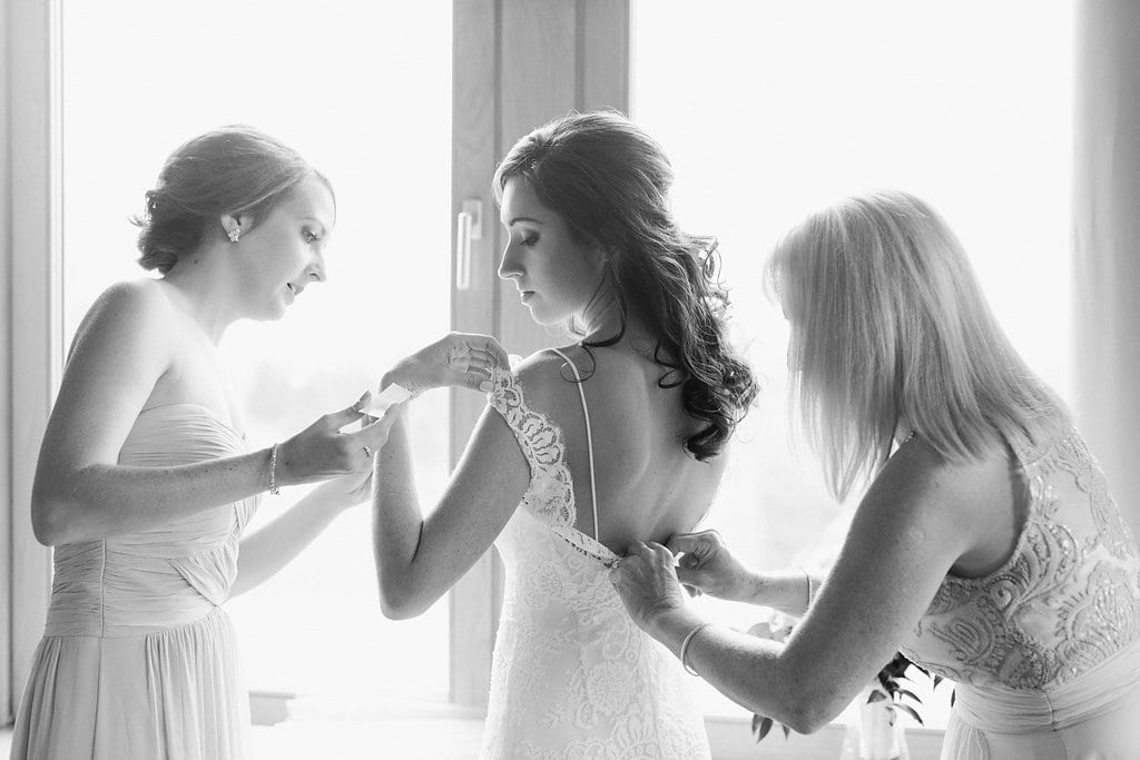 Bride being helped into her wedding dress by mother of the bride and sister