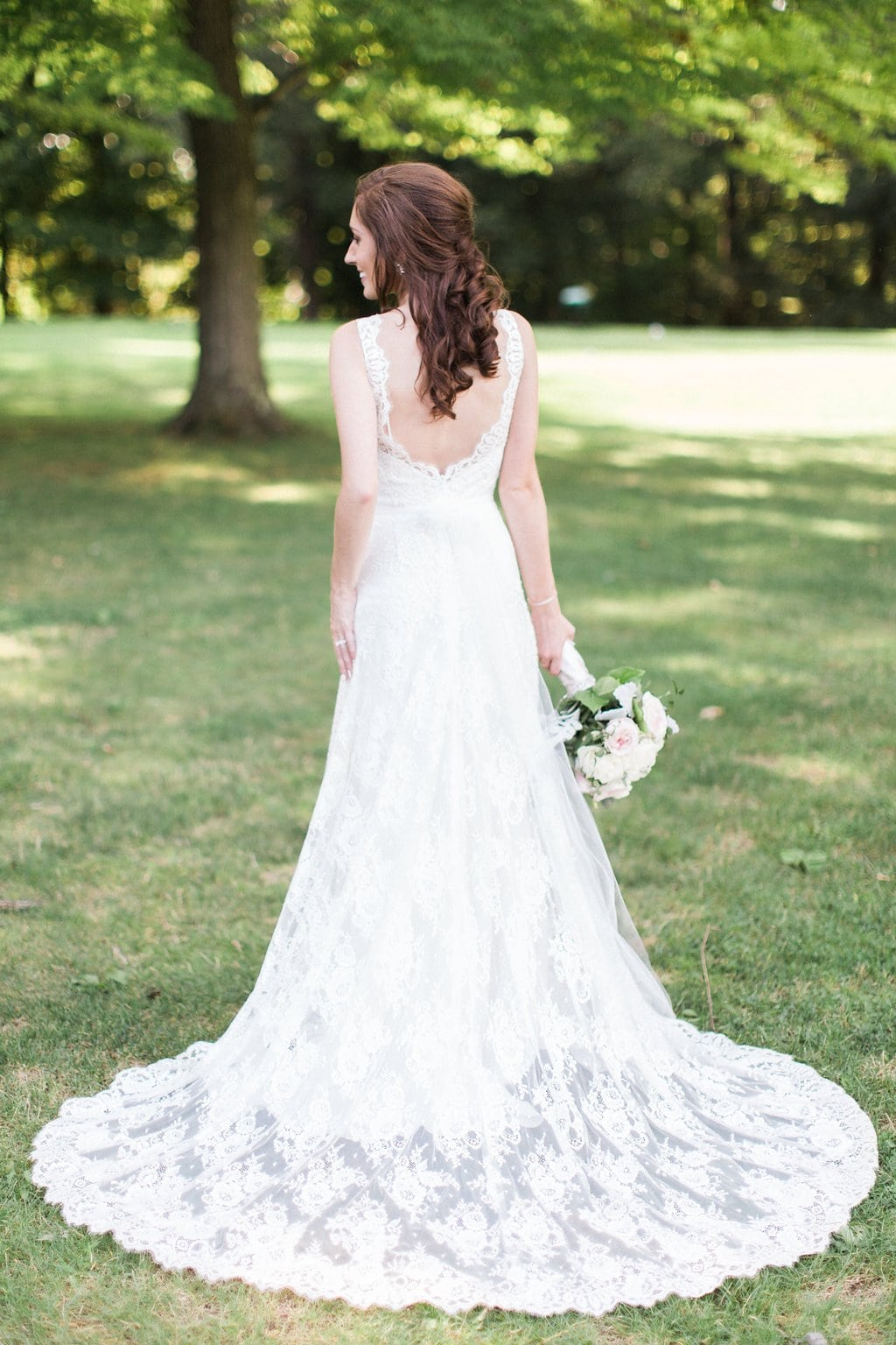 Bridal portrait of back of wedding dress with woman holding bouquet