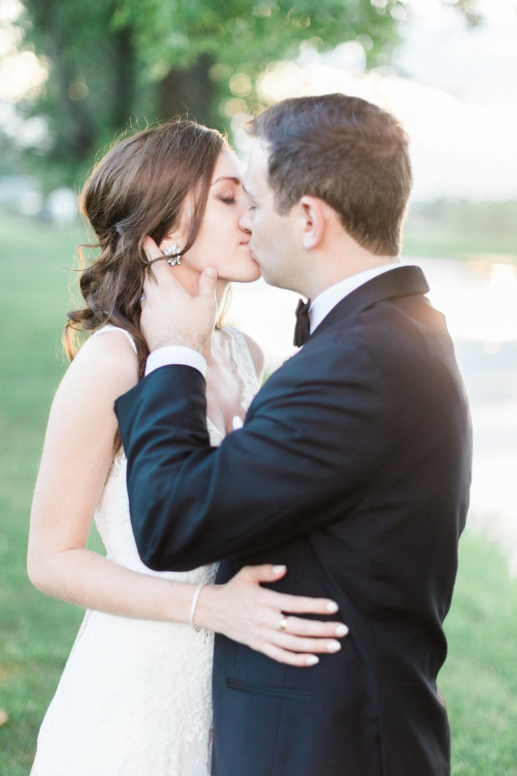 Bride and groom kissing during sunset on golf course