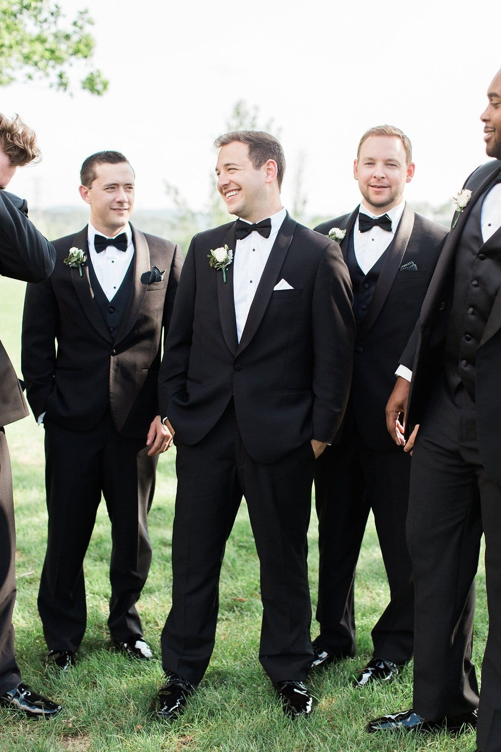 Groom laughing and walking with groomsman