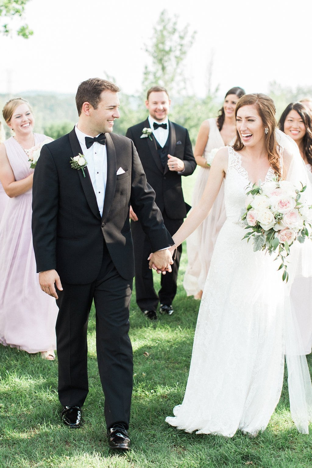 Bride and groom walking and holding hands with wedding party