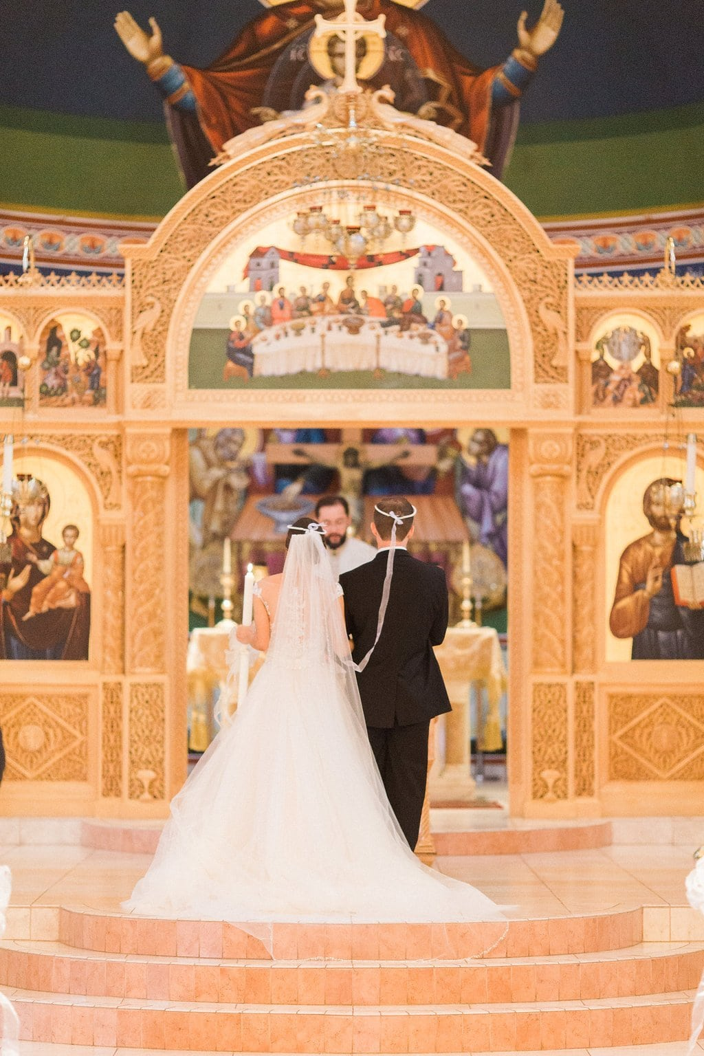 The bride and groom at the alter during their Greek wedding ceremony
