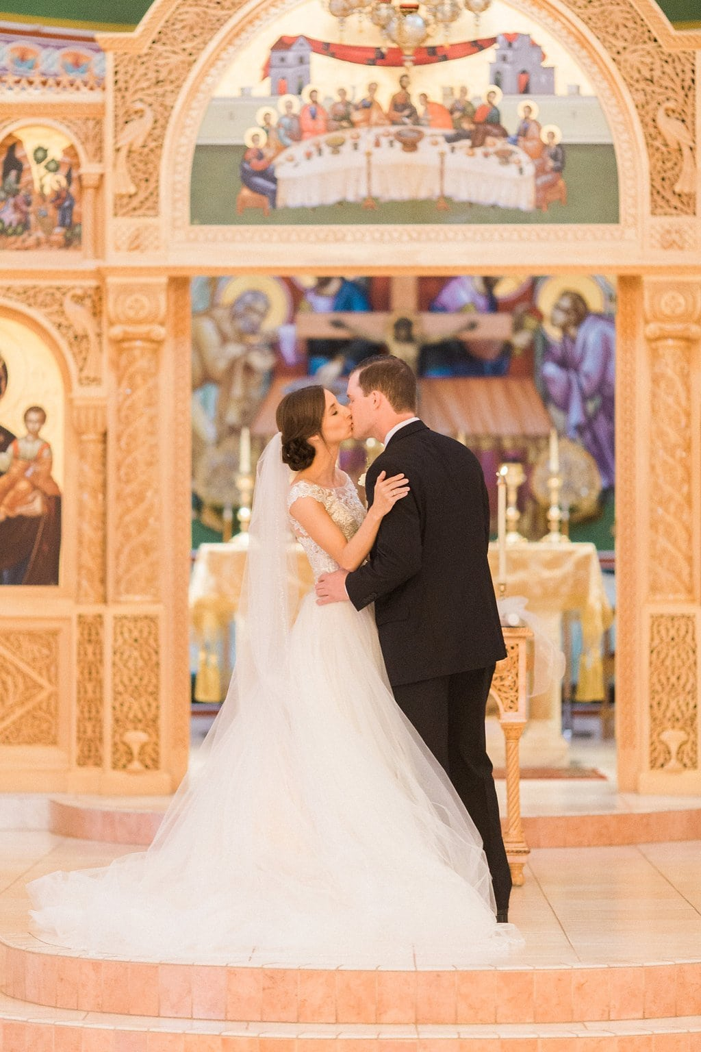 The couple's first kiss at the end of their wedding ceremony at the Greek Church