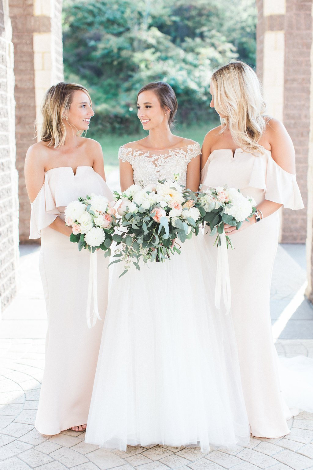 Bridesmaids wearing dresses from revolve clothing photos outside of church with bouquets