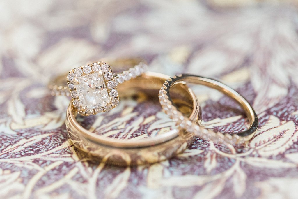 Wedding bands and engagement ring in yellow gold with diamond halo photograph
