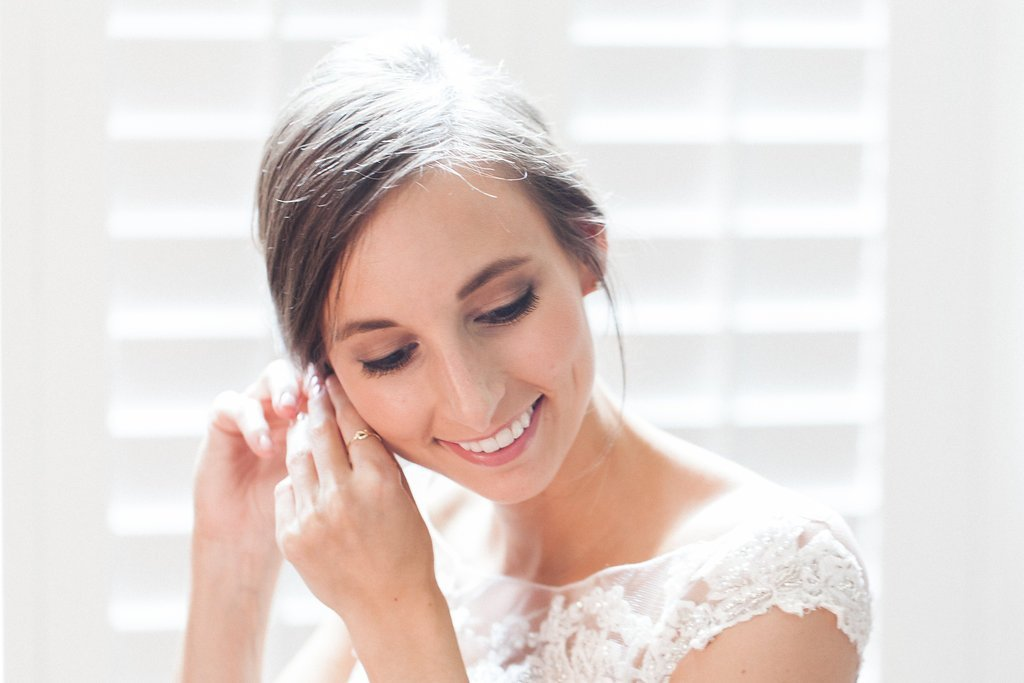 Bride putting her earrings on while getting ready for her wedding day
