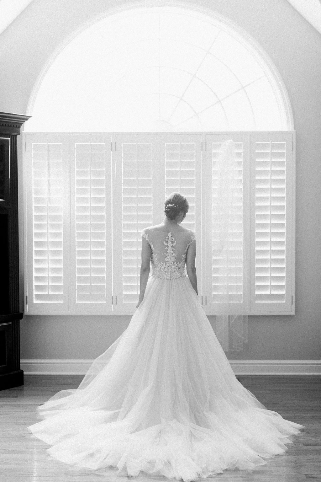 Black and white photograph of bride getting ready for her wedding in her dress