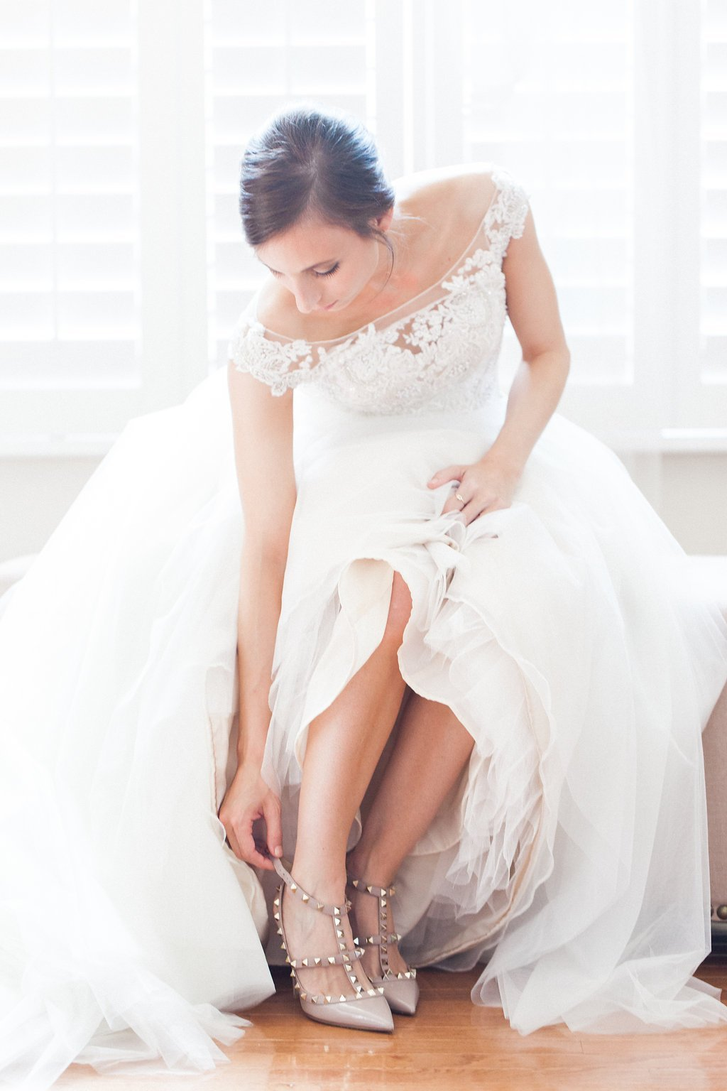 Bride putting on her Valentino Rockstud shoes while getting ready before her wedding